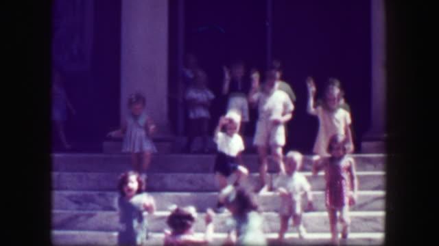 1949:-Kids-leaving-school-walk-down-slick-stone-staircase-with-no-handrails-teachers-follow-
