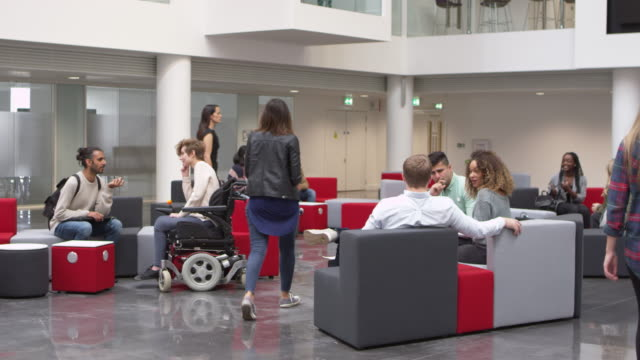 Low-angle-view-of-students-in-a-busy-university-lobby-area-shot-on-R3D