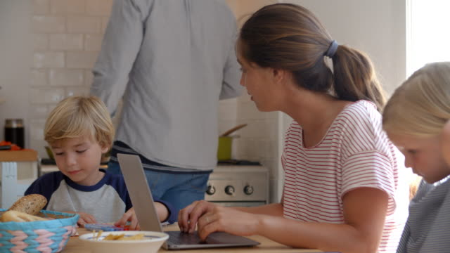 Kids-working-at-kitchen-table-with-mum-while-dad-cooks