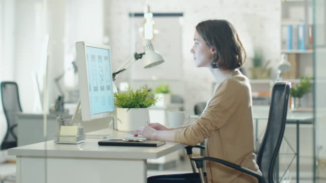 Creative-Brunette-Working-on-Design-at-Her-Desktop-Computer-Sitting-in-Her-developer-Office-