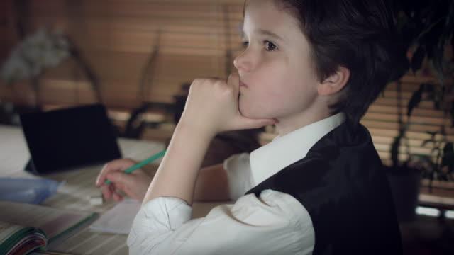 4K-Hi-Tech-Shot-of-a-Child-Doing-Homework-Thinking-and-He-Got-an-Idea