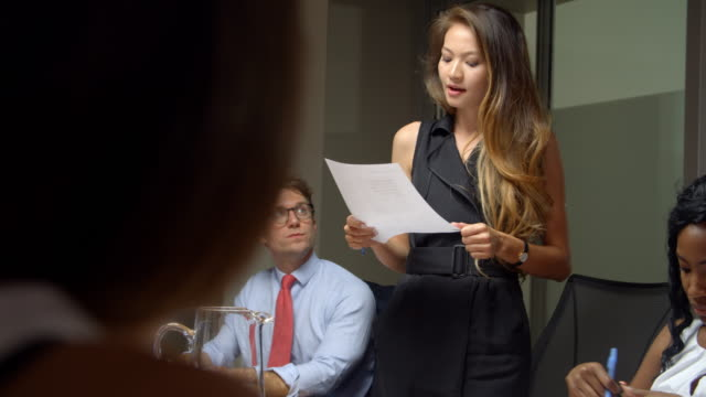 Asian-woman-stands-to-address-colleagues-at-business-meeting