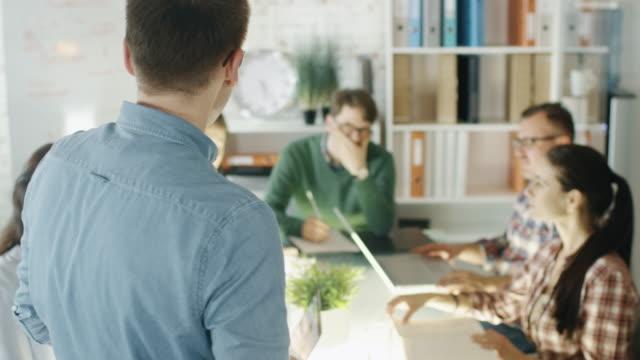 El-joven-ejecutivo-adresses-a-sus-colegas-en-una-sesión-de-planificación-estratégica-Él-está-parado-y-los-compañeros-de-trabajo-están-sentados-en-la-gran-mesa-de-conferencias-escuchándole-cuidadosamente-Cámara-lenta-