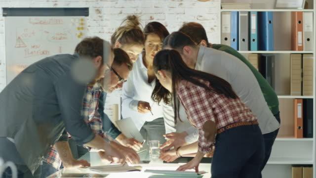 Siete-personas-con-estilo-de-pie-diversa-se-inclinan-en-una-mesa-de-conferencias-mientras-hablan-enérgicamente-de-los-planes-de-negocios-diarios-