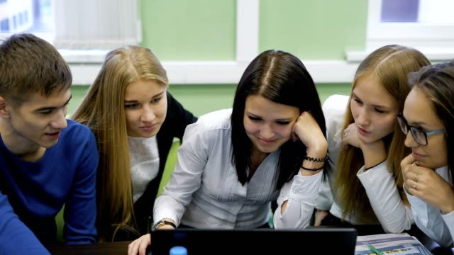 High-school-students-sitting-in-front-of-a-computer-monitor-and-having-fun