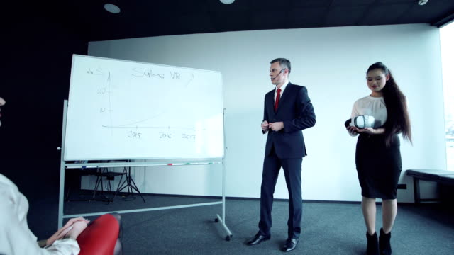 Businessman-says-showing-charts-on-a-whiteboard