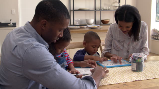 Parents-And-Children-Drawing-On-Whiteboards-At-Table
