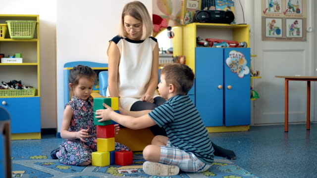 Two-toddler-children-build-tower-of-colorful-plastic-blocks