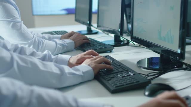 Grupo-de-personas-trabajando-en-oficina-brillante-Toma-de-las-manos-escribiendo-mientras-trabajaba-en-el-equipo-