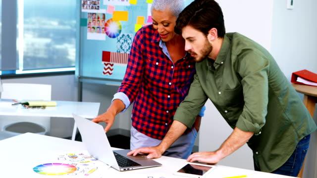 Diseñadores-gráficos-discutiendo-sobre-laptop