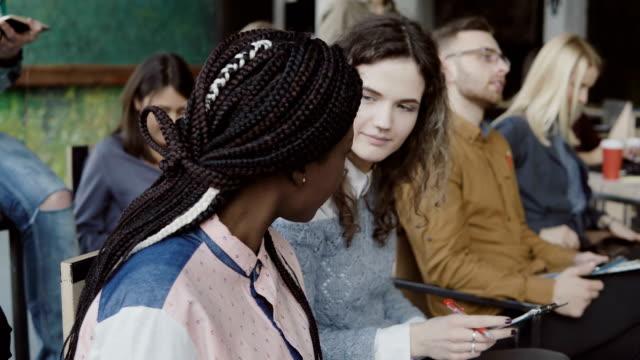 Junge-kreative-Business-Team-in-Konferenz-im-modernen-Büro-Zwei-Kollegen-afrikanischen-und-kaukasischen-Frau-im-Gespräch
