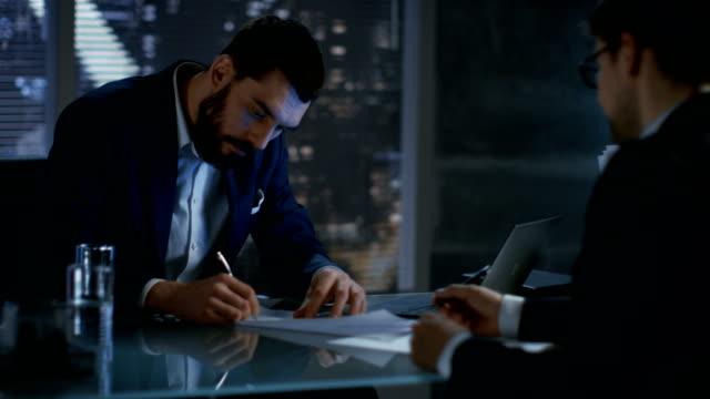 Tarde-noche-empresario-empresario-tiene-conversación-con-el-cliente-importante-llegan-a-un-acuerdo-contratación-de-ambos-signos-En-la-ventana-de-fondo-grande-de-la-ciudad-