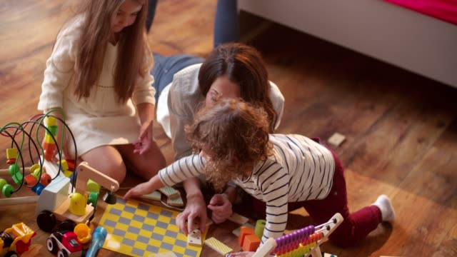 Young-children-playing-messily-with-their-mother-on-the-floor