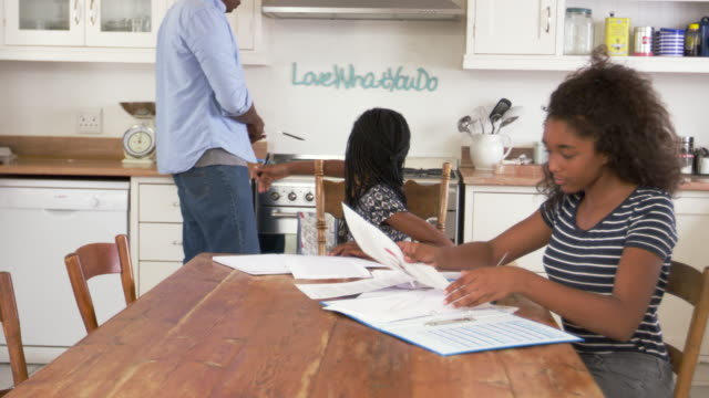 Father-Helping-Two-Daughters-Sitting-At-Table-Doing-Homework