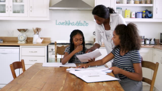 Mother-Helping-Two-Daughters-Sitting-At-Table-Doing-Homework