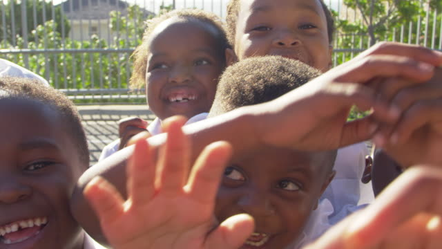 Young-school-kids-in-playground-wave-to-camera-slow-motion