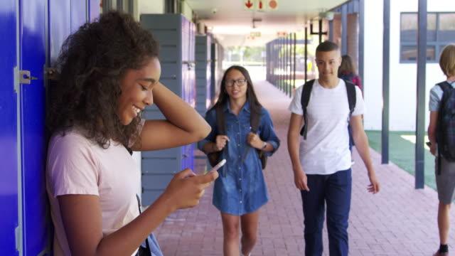 Three-teenage-friends-talk-in-school-corridor-slow-motion