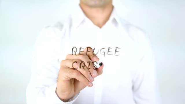 Refugee-Crisis-Man-Writing-on-Glass