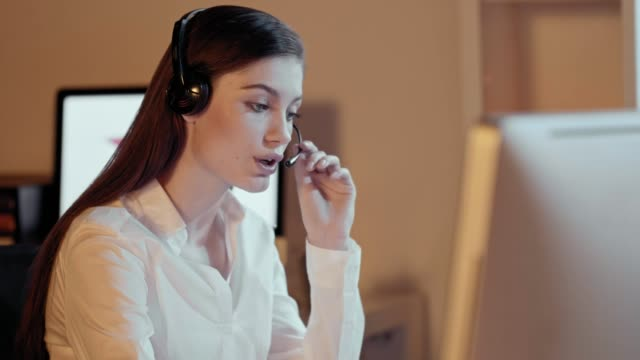 Attractive-professional-woman-with-a-lovely-radiant-smile-wearing-a-headset-and