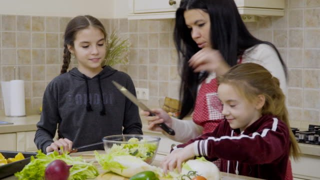 Little-girls-help-mother-to-cook-salad-for-dinner