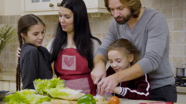 Father-and-daughter-cuts-the-onion-for-salad