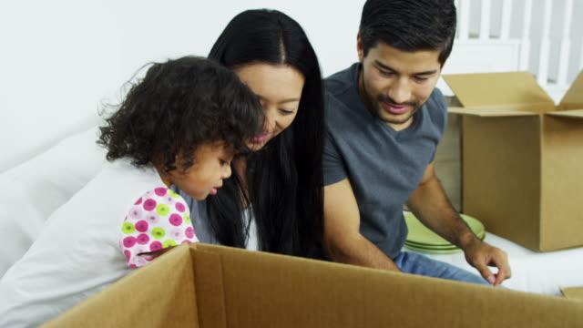 Étnico-de-los-padres-a-hija-jugando-en-casa