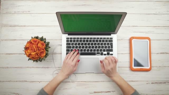 Freelance-de-mujer-inserta-un-auriculares-en-un-ordenador-portátil-de-pie-sobre-la-mesa-de-madera-blanca-con-flores-y-naranja-tableta-y-trabaja-en-él-Vista-superior-Cerca-de-las-manos