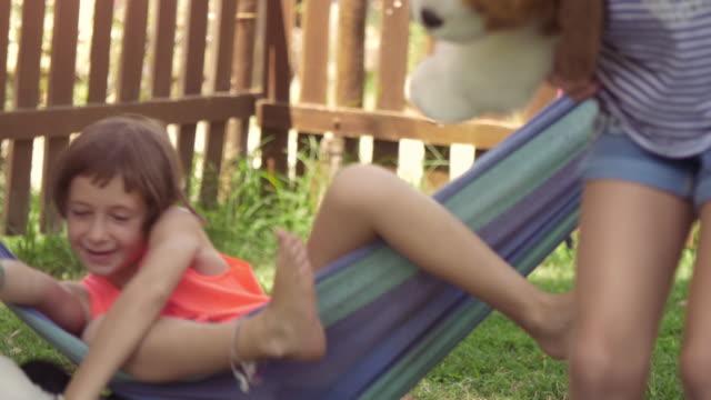 Jóvenes-felices-niñas-en-campamento-de-verano-en-coloridas-hamacas-relajantes-jugando-afuera-con-muñecas-de-perro-de-felpas-en-la-hierba-verde-campo-niños-niños-lenta