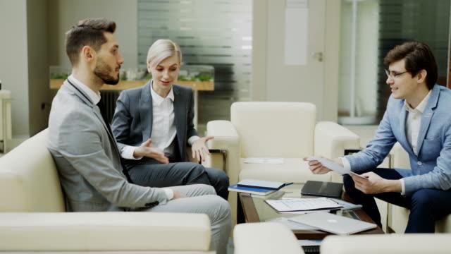 Toma-panorámica-del-empresario-sobre-los-informes-financieros-con-socios-femeninos-y-masculinos-sentado-en-el-sofá-en-el-hall-de-la-oficina-moderna-con