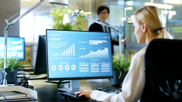 In-the-Office-Businesswoman-at-Her-Desk-She-s-Using-Personal-Computer-with-Statistical-Information-Showing-on-It-s-Screen-Her-Colleague-Sets-Opposite-to-Her-
