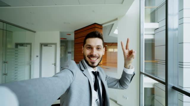 POV-jungen-Geschäftsmann-im-Anzug-Selfie-fotografieren-und-amüsieren-Sie-sich-im-modernen-Büro