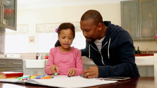 Padre-e-hija-jugando-con-lápices-de-colores-de-color-4k