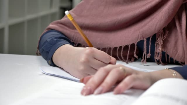 Beautiful-female-hands-write-in-a-notebook-Pencil-Manicure-Close-up-Arab-women-in-the-office-60-fps