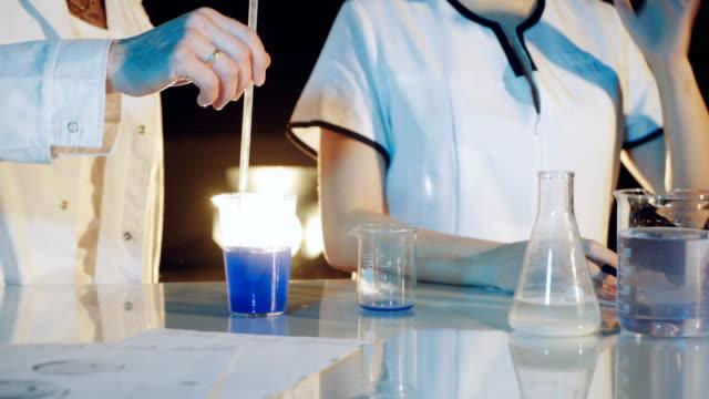Profesional-químico-en-una-bata-de-laboratorio-está-experimentando-mediante-la-mezcla-de-productos-químicos-líquidos-en-frascos-