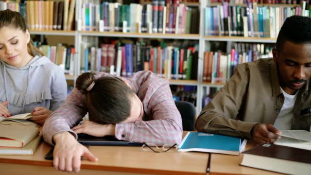 Pan-Schuss-von-fleißigen-Studenten-Prüfungsvorbereitung-tun-Hausaufgaben-und-müde-Kerl-schlafen-auf-Tabelle-in-der-Universitätsbibliothek
