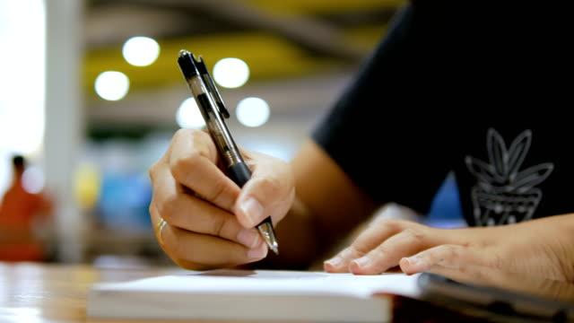 Cerrar-tiro-mano-de-escritura-en-papel-cuaderno-seleccione-enfoque-profundidad-de-campo-de-la-mujer