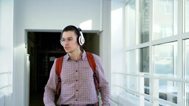 Joven-estudiante-masculino-guapo-caminando-bailando-en-el-corredor-largo-ancho-vidrioso-reunión-sus-groupmates-multiétnica-dándoles-cinco-y-seguir-adelante-positivamente