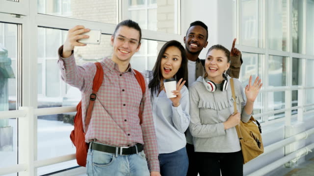 Group-of-four-multi-ethnic-positive-male-and-female-students-are-standing-in-wide-corridor-Hipster-gut-is-holding-smartphone-making-selfie-of-them-all