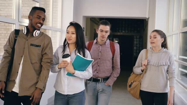 Vier-Kollegen-unterschiedlicher-ethnischer-Herkunft-sind-Fuß-in-lange-geräumigen-weiten-gläsernen-Korridor-in-Universität-Lächeln-und-lachen-und-reden-miteinander