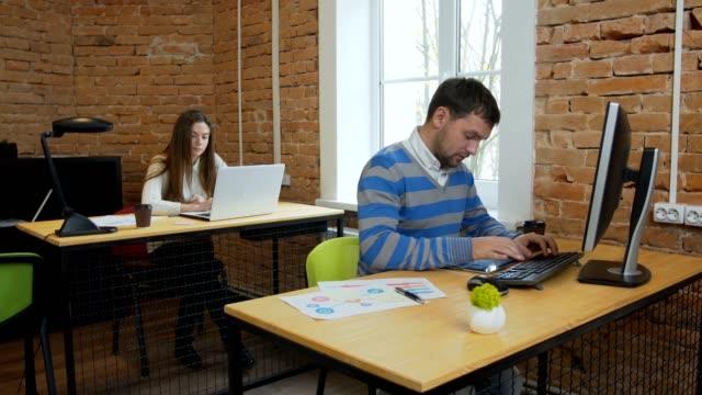 Closeup-Porträt-einer-schönen-jungen-Frau-und-Mann-die-auf-dem-Computer-im-Büro-arbeiten-