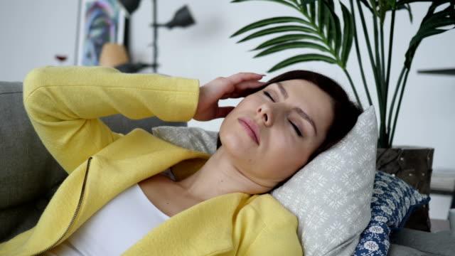 Kopfschmerzen-angespannte-Frau-Verlegung-auf-Sofa-zu-Hause
