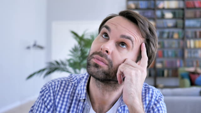 Pensive-Casual-Beard-Man-Thinking-and-Working-on-Laptop-4k-high-quality