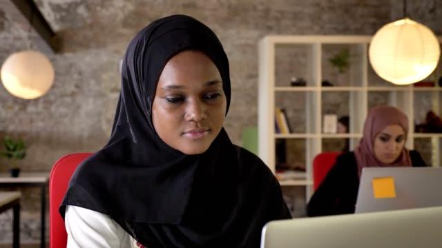 Retrato-de-jóvenes-negros-musulmanes-hijab-trabajando-en-ordenador-portátil-concentrado-dos-encantadoras-mujeres-sentado-en-la-oficina-moderna