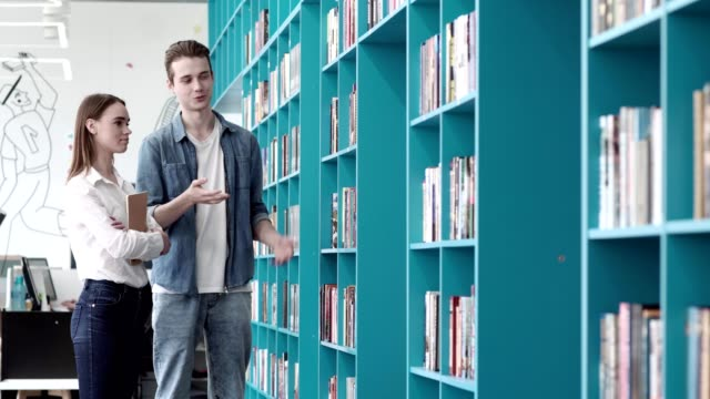 Young-man-and-woman-standing-by-shelevs-in-library-and-choosing-books-Man-telling-about-his-favorite-books-to-girlfriend