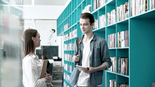 Dolly-in-shot-of-two-university-students-boy-and-girl-having-friendly-talk-near-bookshelves-in-library