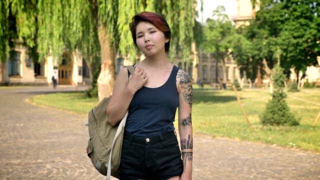 Young-asian-female-student-with-tattoo-standing-with-backpack-and-looking-in-camera-in-park-near-university-confident