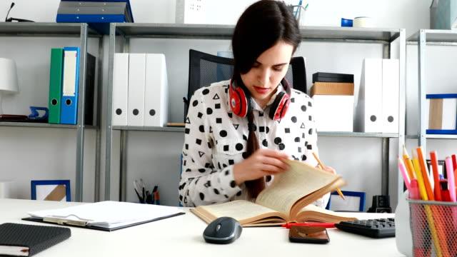 mujer-con-auriculares-rojo-con-hombros-hojeando-el-libro-y-escribir-en-lápiz-sobre-papel