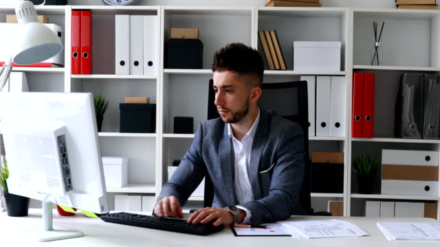 businessman-in-gray-jacket-sitting-at-table-in-white-office-printing-on-the-keyboard-and-throwing-papers