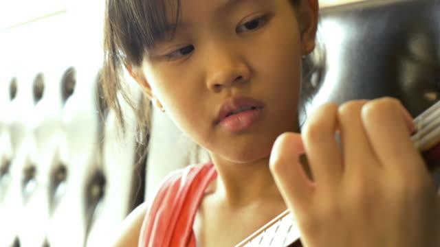 Little-Asian-child-playing-ukulele-on-sofa