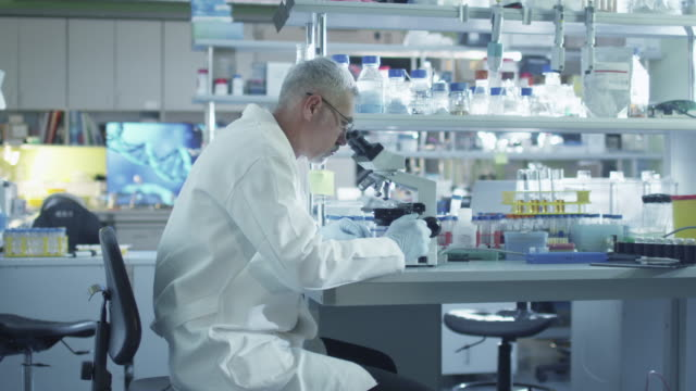 Male-scientist-is-working-on-a-microscope-in-a-laboratory-
